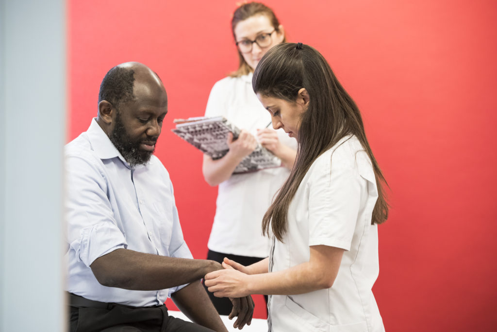 Osteopath treating patient with observer present